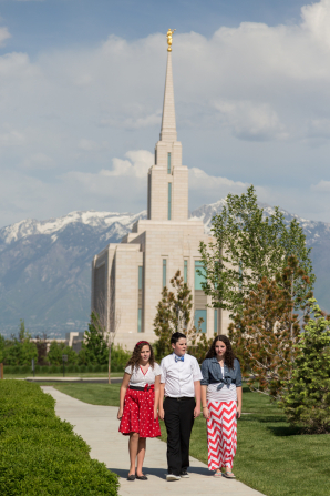 A young man wearing a bow tie walks between two young women around the grounds of the Oquirrh Mountain Utah Temple.