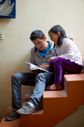 A young man in jeans and a pullover sits on the steps while his little sister, in purple pants and a flowered shirt, sits on a step above him and reads along with him in the Book of Mormon.