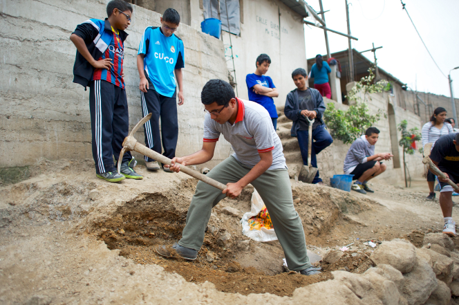 A young man uses an ax to dig in the dirt during a service activity in Peru, with many other youth working together in the background.