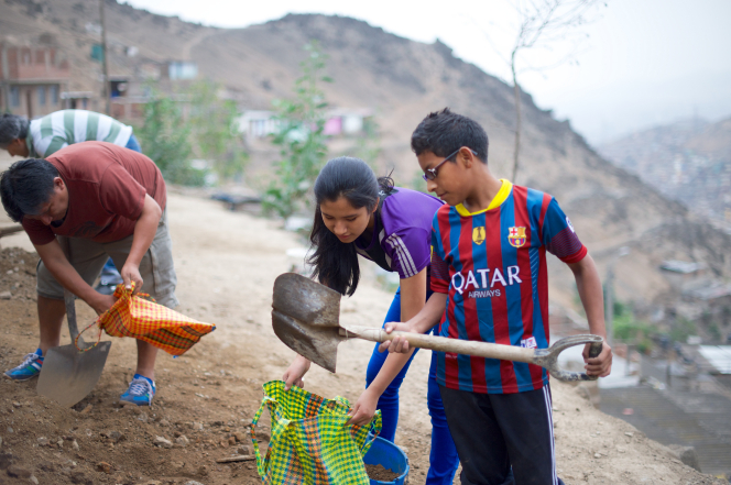 A young man in Peru, wearing a soccer jersey, shovels dirt into a bag that a young woman is holding open while other men in the background use shovels to dig up dirt.