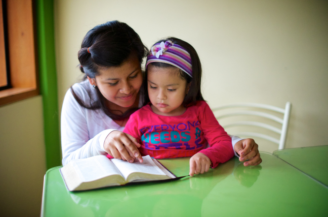 A young black-haired woman sits at a table with her younger sister while they read the scriptures together.