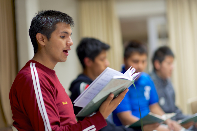 A young man in Peru holds open a hymnbook and sings from it during a Mutual activity, with several other young men doing the same in the background.