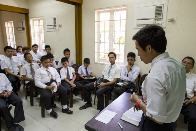 A young man in a white shirt and tie stands to teach a classroom full of young men in white shirts and ties, all sitting down, during a priesthood meeting.