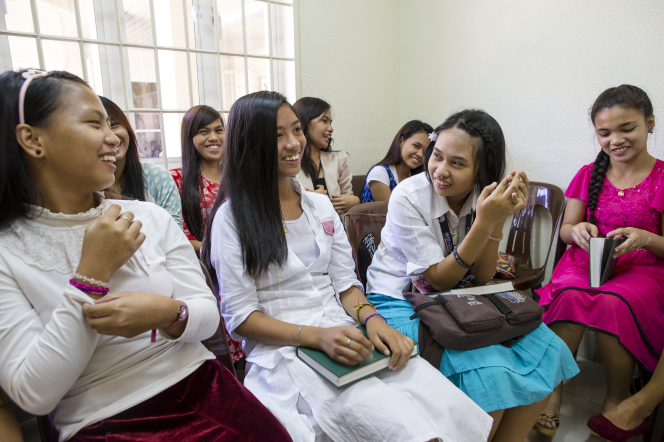 A group of at least eight young women in the Philippines sits in a classroom together at church, with hymnbooks and scriptures on their laps.