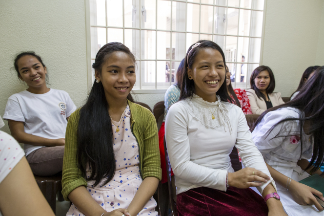 A group of young women in the Philippines, all in dresses and skirts, sits in a classroom together and smile.