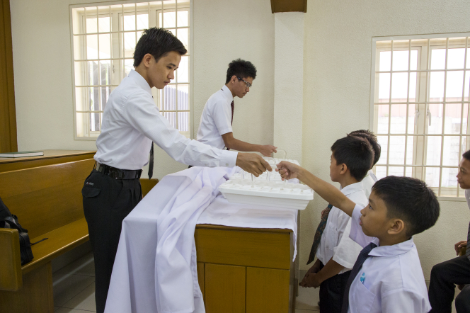 Two young men hand trays with water to young men so they can pass the sacrament to the congregation in a chapel in the Philippines.