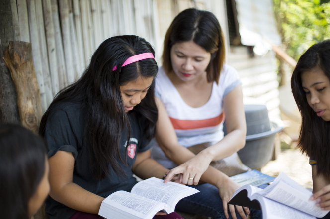 A woman sits outside next to a younger girl and reads the scriptures with her, with two other young women sitting nearby.