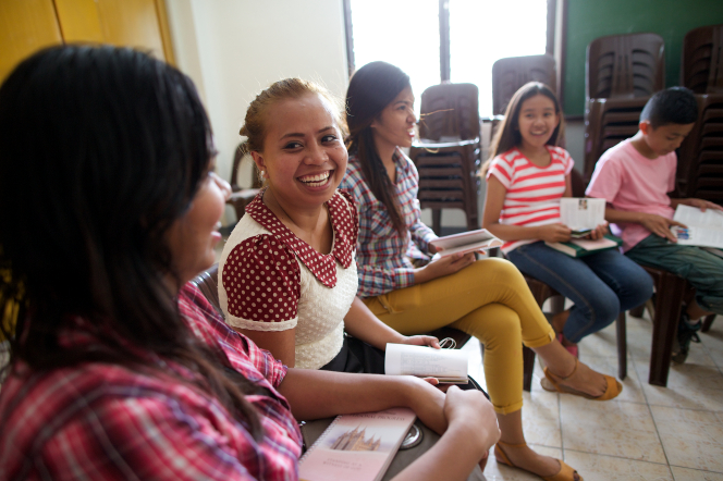 A group of young women from the Philippines sitting in a row and smiling while working in their Personal Progress books.