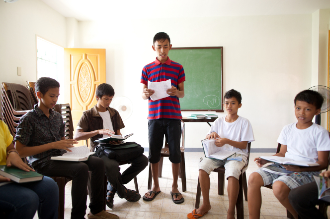 A group of young men from the Philippines sitting in a circle in a Sunday School class, looking through hymnbooks while one young man stands and reads to them.