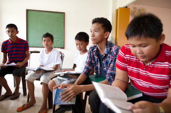 A group of young men from the Philippines sitting in a circle, looking at various Church books, with a chalkboard in the background.