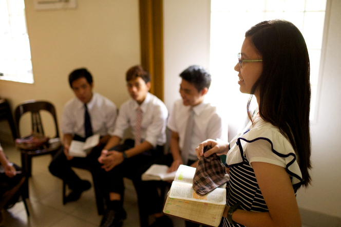 A young woman in glasses stands in front of her Sunday School class of other young men and young women, holding her scriptures open.