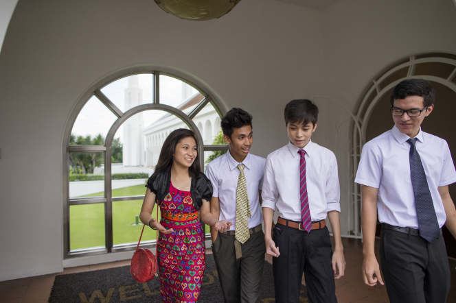 A young woman in a dress walks around the grounds of the Manila Philippines Temple with three young men in white shirts and ties.