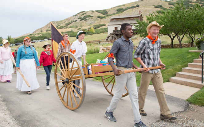 Two young men wearing kerchiefs pull a handcart while other young men and young women follow behind and carry a flag.