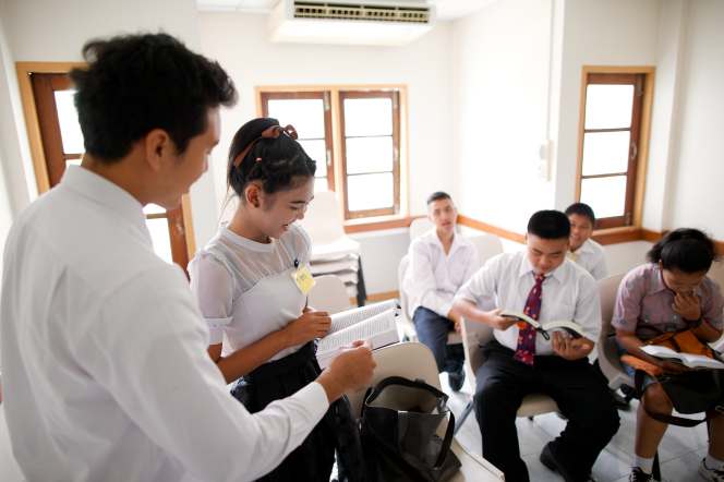 A young man and a young woman stand up in front of their class of other young men and young women and read from a set of scriptures.