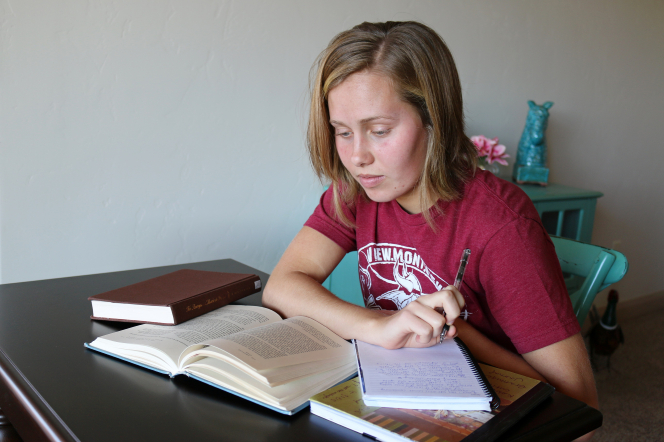 A young woman with short blonde hair sits with a pen in her hand at a desk with an open book, a journal, and a set of scriptures.