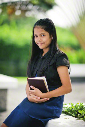 A young woman with long black hair, a black shirt, and a blue skirt sits on the grounds of a temple in the Philippines, holding a set of scriptures and smiling.