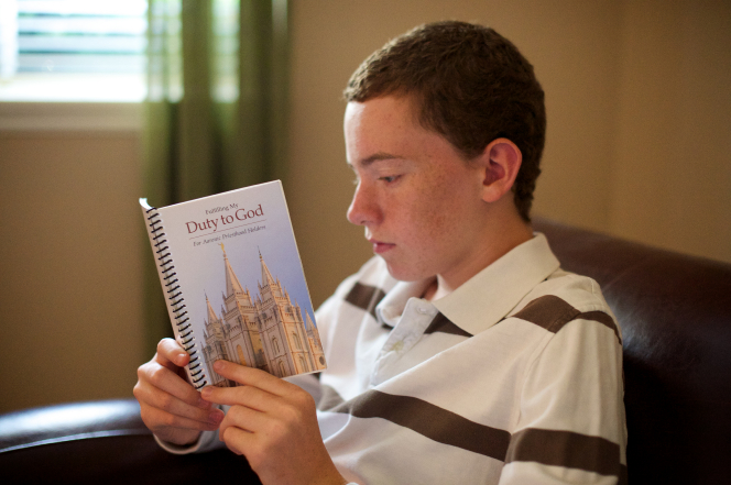 A young man in a brown and white striped polo shirt sits in a brown armchair, reading the booklet Fulfilling My Duty to God.