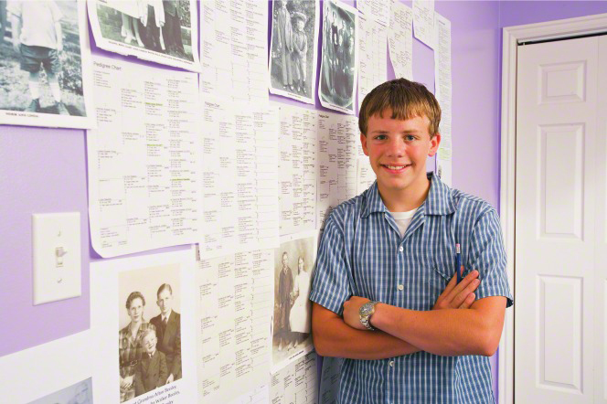 A young man with short blond hair and a plaid shirt folds his arms, smiles, and leans against a purple wall that is covered in pedigree charts and photographs of his ancestors.