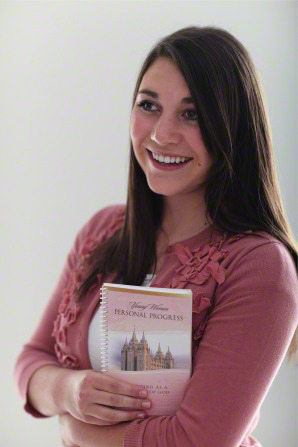 A young woman with long dark brown hair and a rose-colored sweater holds her Personal Progress book in her arms and smiles.