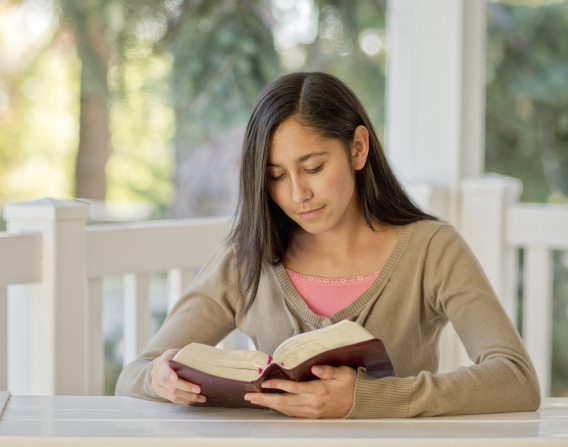 A young woman with long brown hair, a light brown cardigan, and a pink shirt sits at a table on her porch and reads her scriptures.