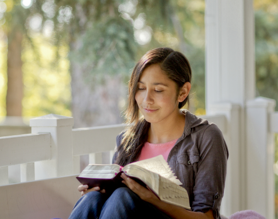 A young woman sits on her porch and reads from a set of scriptures.