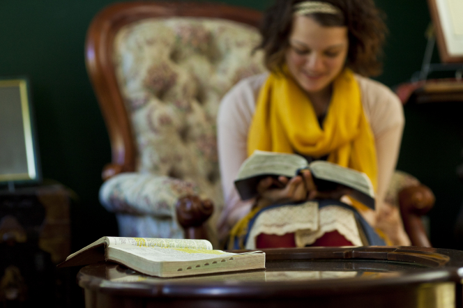 A young woman with short brown hair and a yellow scarf holds open a set of scriptures in her lap, with another set of scriptures open on a table in the foreground.