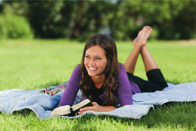 A young woman with long brown hair and a purple shirt lies outside on a blue blanket with her scriptures open in front of her.