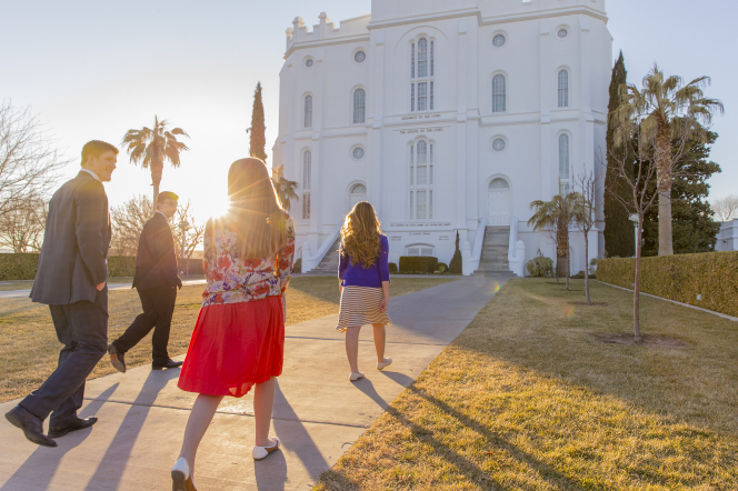 Two young women and two young men in Sunday dress walk toward the St. George Utah Temple during sunset.