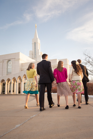 A mother and father and their three teenage children, all in Sunday dress, walk toward the Bountiful Utah Temple.