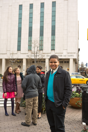 A young man in a coat and tie stands in front of the Manhattan New York Temple and smiles.