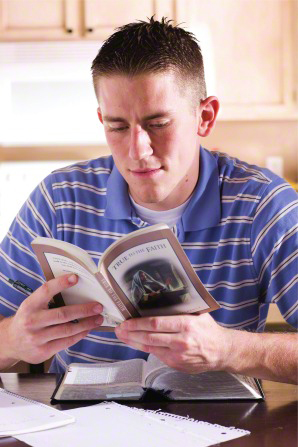 A young man in a blue striped polo shirt sits and reads True to the Faith, with his scriptures open on the table in front of him.