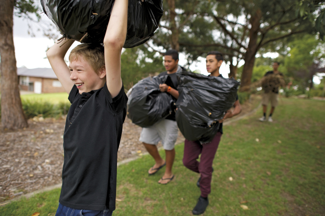 A young man in a black shirt smiles while holding a black garbage bag full of leaves over his head.
