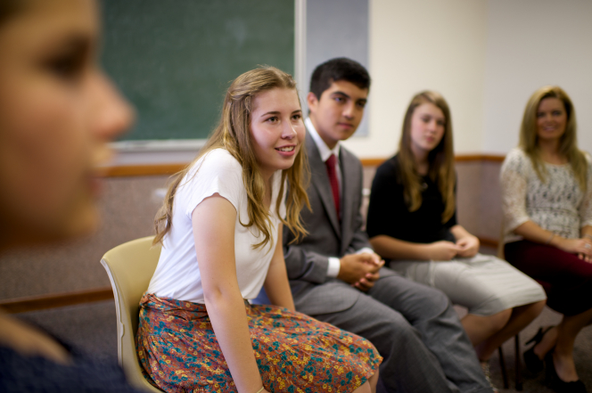 A young woman with long blonde hair and a flower print skirt sits in a Sunday School classroom with one young man and three other young women.