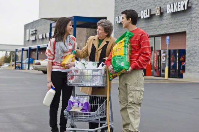 A young man carries a large bag and a young woman carries orange juice and milk for an elderly woman as she pushes her grocery cart in a parking lot.