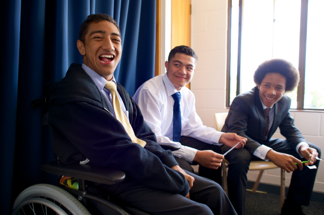 One young man in a suit and tie sits in a wheelchair, with two other young men sitting next to him and smiling.