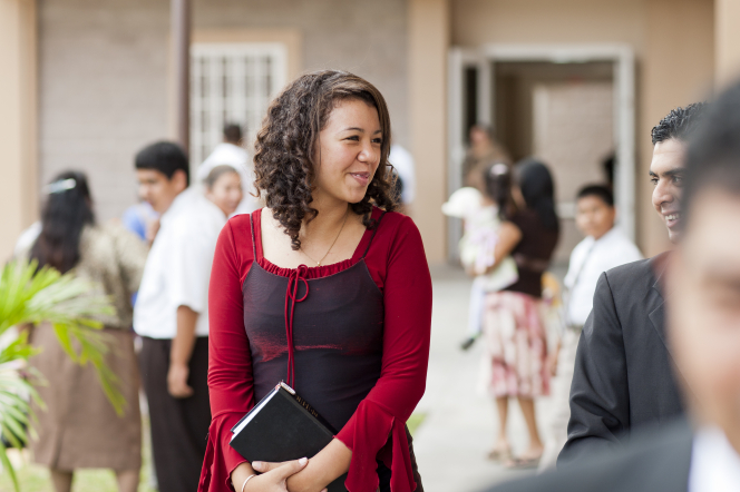 A young woman with curly hair stands outside of a Church building in El Salvador, holding scriptures in her hands.