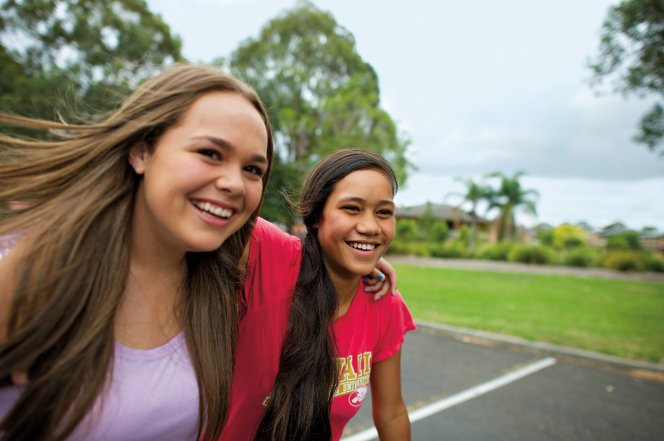 A young woman with long brown hair and a purple shirt puts her arm around another young woman with long dark brown hair and a T-shirt as they walk together and smile.