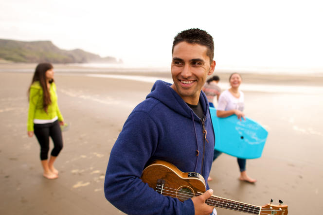 A young man in a blue hoodie walks along the beach, carrying an ukulele, with three other young women walking behind him, one carrying a bodyboard.