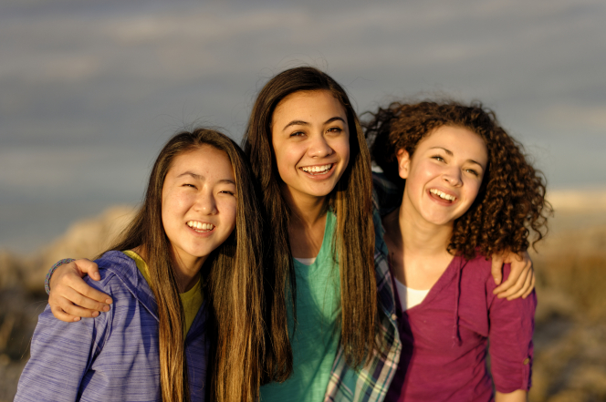 A young woman with long brown hair and a green shirt puts her arms around two other girls on either side of her.