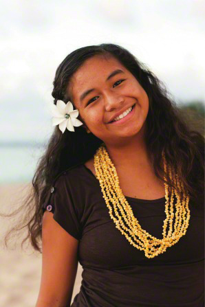 A young woman with a white flower in her long, brown, wavy hair, wearing a yellow beaded necklace, smiling.