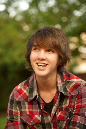 A portrait of a young man with somewhat long brown hair and a plaid shirt, looking up and smiling while sitting outside.