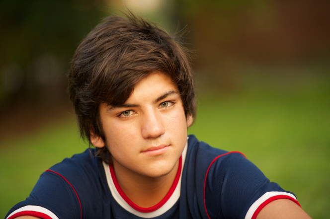 A portrait of a young man in a sports jersey sitting outside and looking straight ahead.