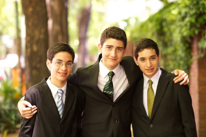 A portrait of three young men in black suits, white shirts, and ties, standing side by side outdoors.