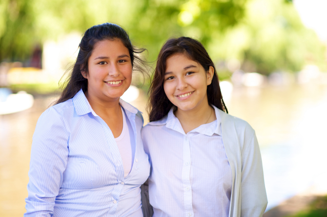A portrait of two young sisters from Argentina, standing side by side outdoors and smiling. They are wearing light-colored shirts.