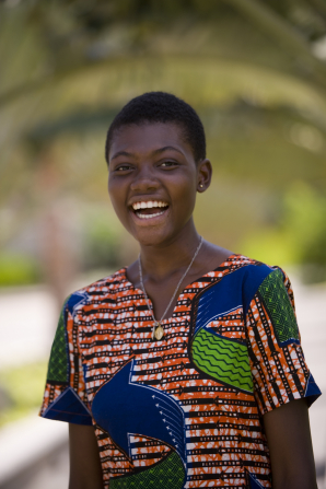 A portrait of a young woman from Ghana in traditional clothing, standing outside and laughing.