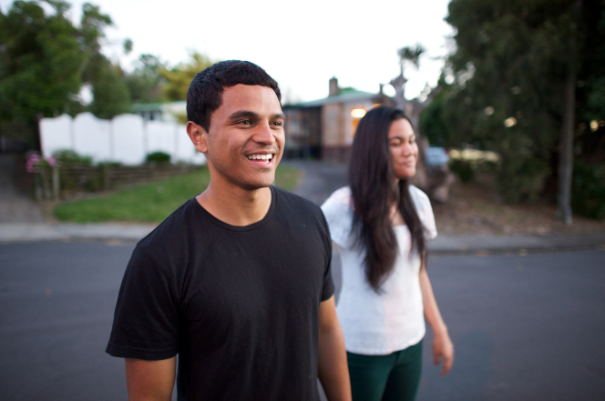 A young man in a black T-shirt smiles while walking outside next to a young woman with long black hair and a white T-shirt.