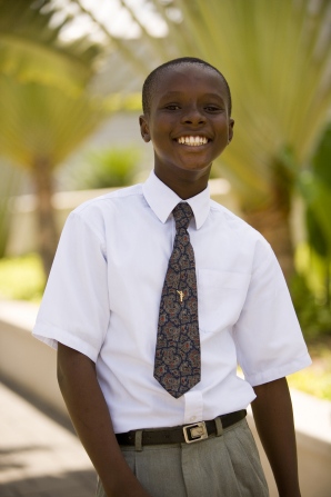 A portrait of a young man in Ghana, wearing a white shirt, a tie, and gray pants, standing outside and smiling.