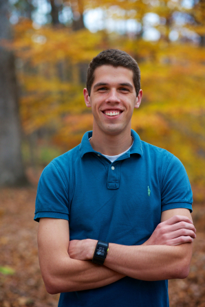 A portrait of a young man in a blue polo shirt with his arms folded, standing outside in the fall and smiling.