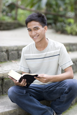 A young man sits outside on steps, holding an open set of scriptures and smiling.