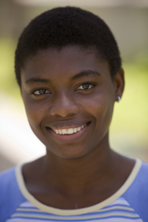 A portrait of a young woman with dark skin and short black hair, wearing a blue shirt.
